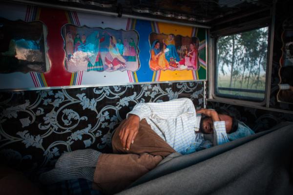Avtar Singh ngủ trong cabin xe tải sau chuyến đi dài xuyên đêm băng qua con đường kém an toàn tại bang Haryana. Cung đường này ngoài hạ tầng giao thông kém, nó còn là nỗi sợ cho cánh tài xế bởi những băng cướp xe tải chuyên nghiệp. Phần lớn thời gian của chuyến đi, các bác tài gói mình vào không gian chật hẹp của cabin.