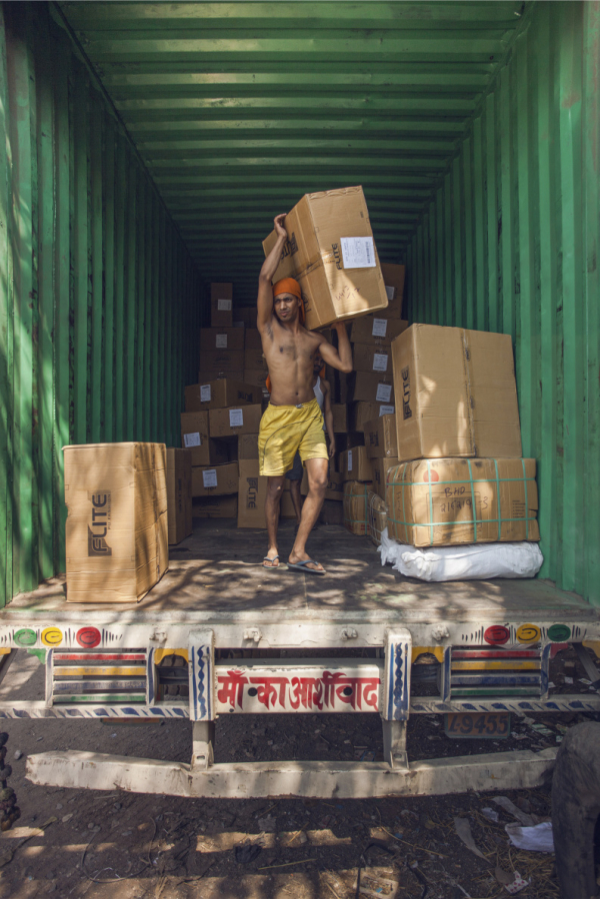 Ở kho xe tải Bhiwandi tại Mumbai, một chiếc xe tải chở đầy hàng hóa không nhãn mác được chuyển đến từ Delhi đang được các cửu vạn dỡ đi nhanh chóng và đưa đến các thương lái đang chờ sẵn.
