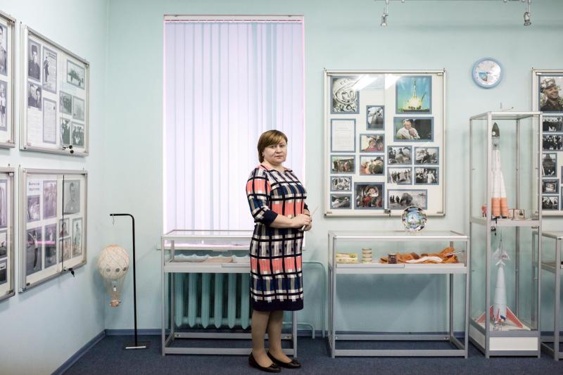 Natalia Tabac, giáo viên hiệu trưởng của một trường học tại làng Gagarin, đang đứng bên cạnh tủ đựng những đồ vật mô phỏng chuyến bay đầu tiên của Gagarin được dùng cho việc giảng dạy.