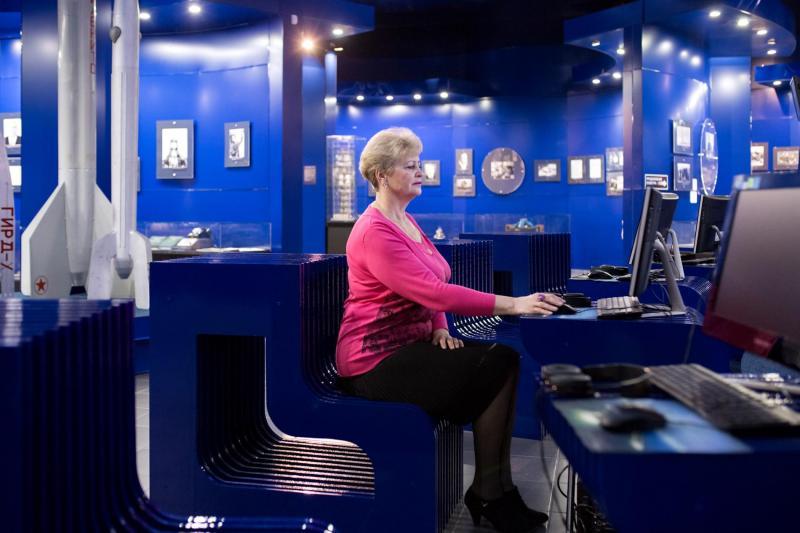 Lyudmila Demina, giám đốc Bảo tàng Chuyến bay Đầu tiên đang ngồi tại khu vực trưng bày chính của bảo tàng.