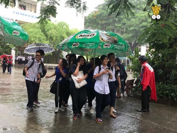 Mưa to sau khi kết thúc môn thi Toán, tình nguyện viên tiếp sức mùa thi đội mưa che dù cho sĩ tử