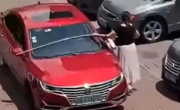 Nữ tài xế cẩn thận dùng thước đo chiều ngang xe xem có vừa với chỗ trống trong bãi đỗ